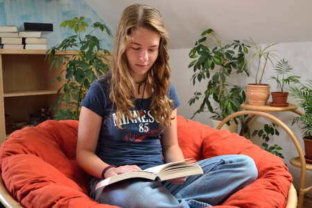 avid: Teenager reads relaxed in rattan Stock Photo