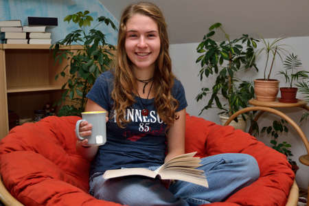avid: Teenagers reading a book and drinking tea while relaxing