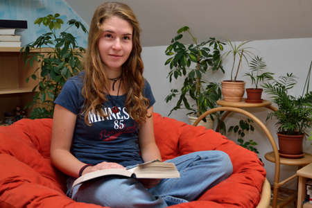 avid: Teenager read comfortably in their favorite book