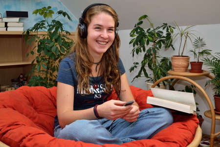 teeny: Teenager listening to music, looking forward and laughs