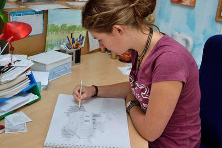 artful: Young woman creates artful pencil drawing Stock Photo