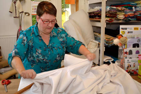 selling service: Saleswoman separates textiles into two halves