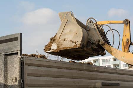 loader: Shovel tilts earth in a low loader