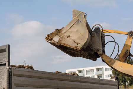 shoveling: Dump truck shoveling earth from construction loaders - Closeup Stock Photo