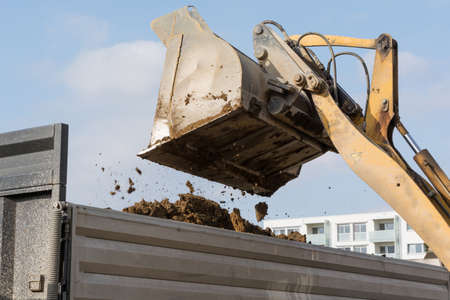 loaders: Excavation tilts earth of construction loaders - Closeup Stock Photo