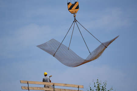 construction mesh: Craftsman on construction site  - steel mesh is transported by crane Stock Photo