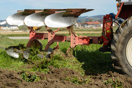 plough machine: With plow meadow is plowed to fresh soil - closeup Stock Photo