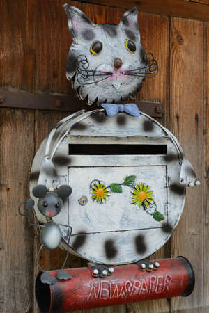 consignment: creative mailbox in design of cat and mouse with newspaper roll Stock Photo