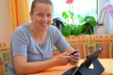 likeable: smiling woman with tablet and phone