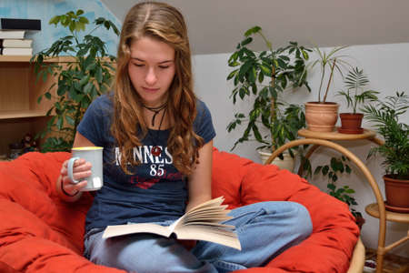 avid: Focused reading a girl a book and drinking tea