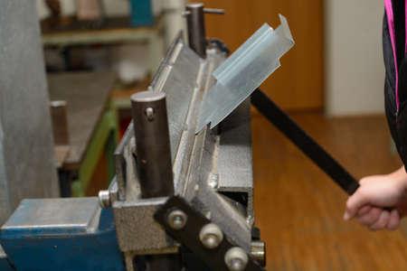 artisanry: Craftswoman processed sheet on a metal bender Stock Photo