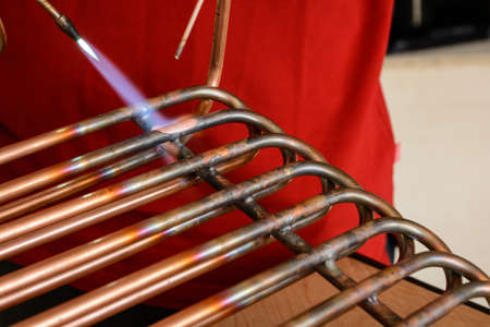 A skilled worker connects copper pipes to the braze - close-up Stock Photo