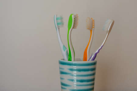 facing each other: Four toothbrushes in ceramic cups facing each other - cropped image