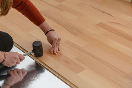 Worker laying a parquet floor - close-up of craftwork