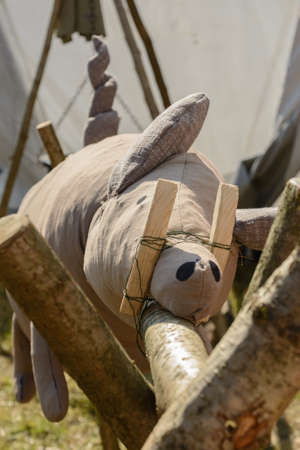 imaginativeness: Decorative stuffed suckling pig on wooden grill - close-up Stock Photo