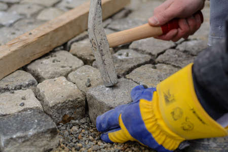 Cobble pavement is placed by a craftsman - close-up