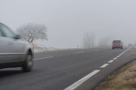 distance: Cars are driving in bad weather in autumn