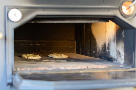 mini oven: Pizzas in an old oven - close-up view in big open oven Stock Photo