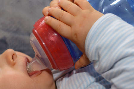 Baby drinking tea from a drinking bottle and holding with both hands the bottle - close-up