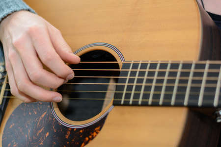 Person plucks song at old Western guitar - close-up Stock Photo