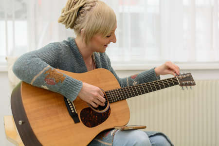 musically: Young smiling woman tunes her western guitar with tuner Stock Photo