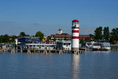 navigational light: Boat landing stage in Podersdorf with lighthouse and church - austria Stock Photo