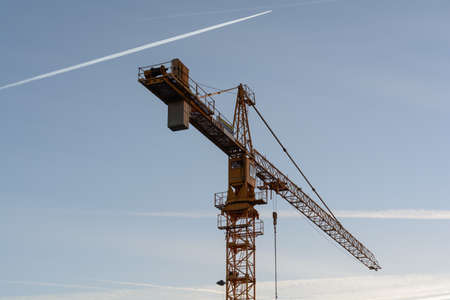 In the foreground an imposing tower crane, behind it blue evening sky with contrails Stock Photo