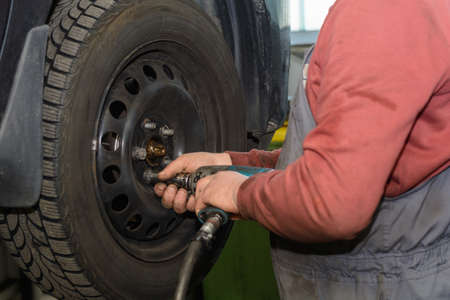 impact wrench: Handyman in tire changing in a power station with impact driver Stock Photo