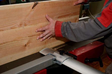 person with a planking board at the planing machine close up stock