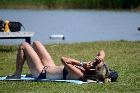 Woman in bikini sunbathing on the sea beach and talking on the phone Stock Photo