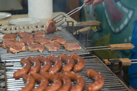 Sausages and meat are prepared on a charcoal grill
