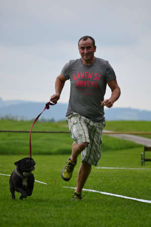Man running with French Bulldog puppy in the dog school