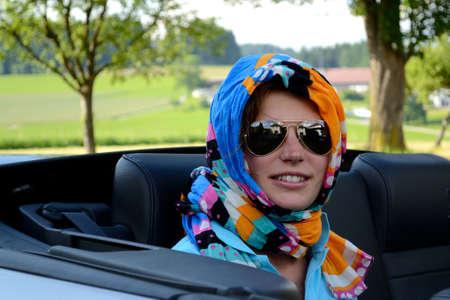 Woman smiles friendly at convertible passenger seat - portrait