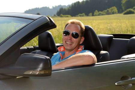 Convertible driver smiles kindly from his car - close-up