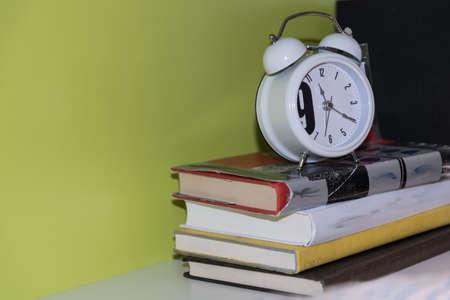 アナログの目覚まし時計 - 書籍のスタックのクローズ アップ