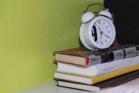 analogue alarm clock on a stack of books - close-up