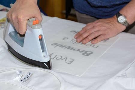 사람이 티셔츠에 겹쳐서 인쇄 된 텍스트로 다림질하고 있습니다.