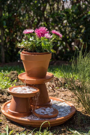 self-made fountain with flower and pebbles as decoration in the garden