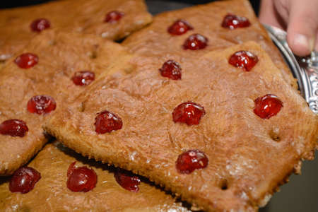 Person holds gingerbread with candied fruit on tray