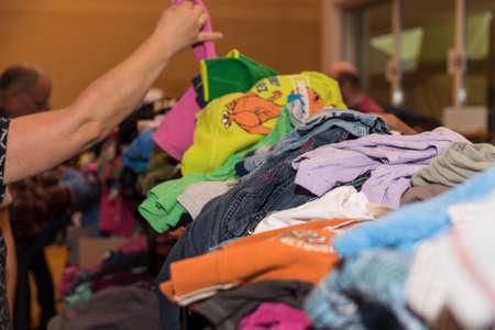 La gente cerca vestiti a buon mercato in un bazar di abbigliamento per bambini Archivio Fotografico - 93652062