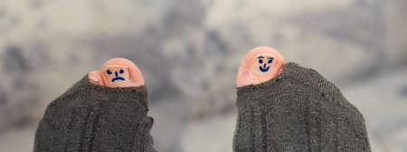 trauriger und fr?hlicher Smiley auf Zehen bei Sockenloch