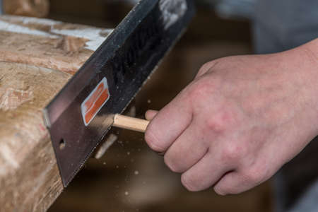 Skilled worker saws wooden dowels with a hand saw - close-up