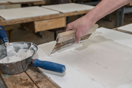Construction worker applies putty to plasterboard with a metal spatula