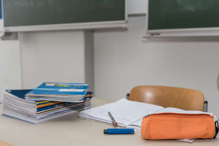 Pile of schoolwork at the teachers desk in the classroom