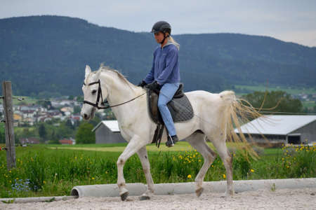 Woman rides at the training ground with her horse - training riding instructor