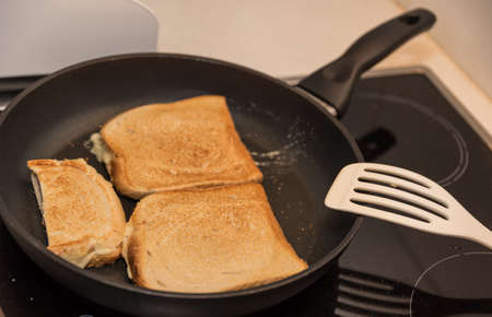 A toast is being prepared in a pan - close up of pancake toast