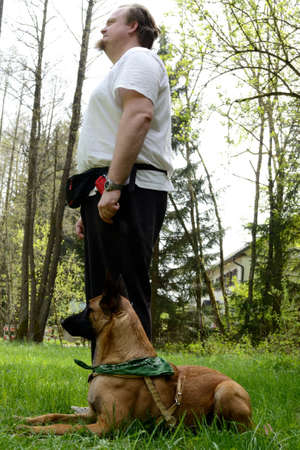 Dog owner with Belgian shepherd dog training to submission and obedience