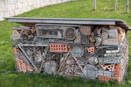 unusually large insect hotel in the garden with various materials