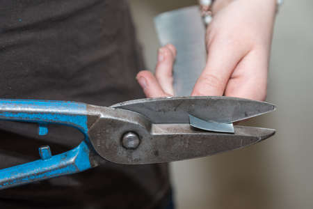 Craftsman in the metal industry works with a plate shears - close-up Stock Photo
