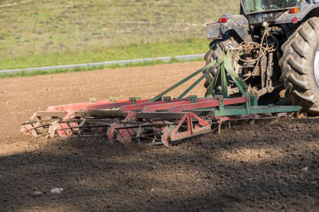Farming a field with tractor and harrow - close-up